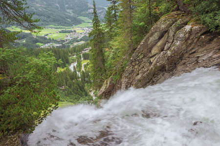 Standing next to the Krimml Waterfalls with Krimml village in the valley on the way to the top of the Krimml Waterfalls
