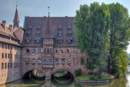 Editorial: NUREMBERG, BAVARIA, GERMANY, August 11, 2020 - View of the Holy Spirit Hospital seen from the museum bridge in Nuremberg. The text on the wall says Holy Spirit Hospital wine bar.