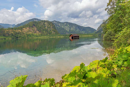 A flooded barn in the Almsee, seen from the southern shore of the lake Archivio Fotografico