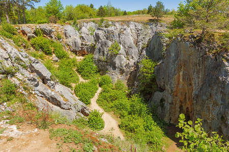 Standing at the edge of the sinkhole of the Fondry des chiens in Nismes. Fondry comes from the French fonderie because iron ore from the sinkhole was melted.