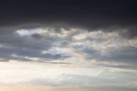 Dark thunder clouds on the blue sky. Abstract background with clouds on blue sky. Banco de Imagens
