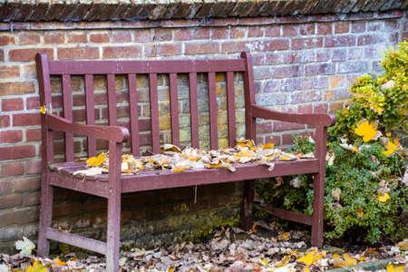 Fallen leaves on wooden bench in empty park autumn background. Bench in autumn landscape Stock fotó