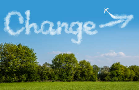 The word Change written with clouds over a green landscape