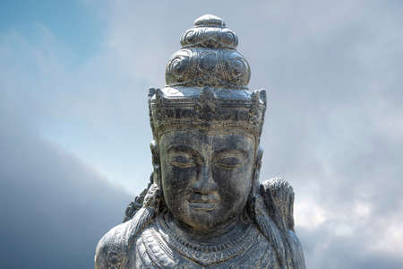 Close-up the Buddha portrait before a bright blue sky. Enlightenment Buddha concept with copy space