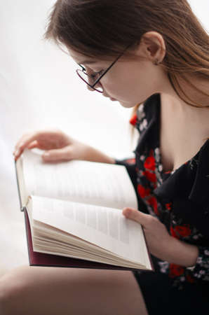 teaches: Beautiful girl sitting at home and reading interesting book. Look in the book