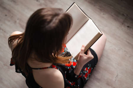 keeping room: A young girl is sitting in a bright room and reading a book