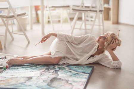 젊은 여자가 바닥에 누워 포즈를 사진 작가