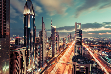 architectural firm: Scenic architecture of downtown Dubai in the evening. Aerial view of famous highway with illuminated skyscrapers. Travel background.