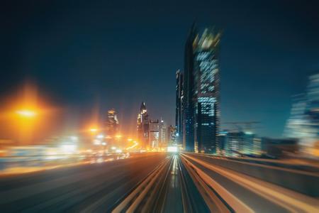 ドバイ、アラブ首長国連邦の照らされたアーキテクチャと夜の街の背景がぼやけています。地下鉄の列車から見た景色します。