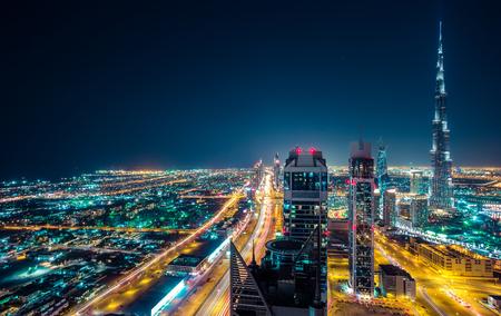 ライトアップされた高層ビル群の幻想的な夜間ドバイのスカイライン。ダウンタウン ドバイ, アラブ首長国連邦の屋上展望。