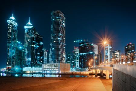 モダンなライトアップされた高層ビル、街灯や霧の橋と美しい夜景。ダウンタウン ドバイ, アラブ首長国連邦. 写真素材