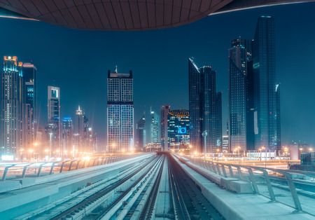 Illuminated modern architecture of Dubais downtown by night seen from a metro train.