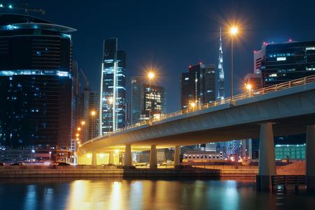 近代的な建物、街灯や橋とドバイの夜間スカイライン。ダウンタウン ドバイ, アラブ首長国連邦.バック グラウンドでブルジュ ・ ハリファ。 写真素材
