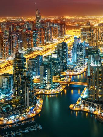 素晴らしいスカイライン: 大都会の建築を点灯します。夜、アラブ首長国連邦のドバイのマリーナ。功妙な旅行の背景。