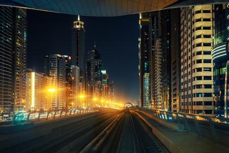 夜のダウンタウン ドバイ。近代的高層ビルや街灯とメトロ車からの眺め。