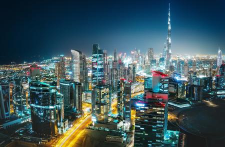 風光明媚な空中夜間都市景観照明のモダンな建築。ダウンタウン ドバイ、アラブ首長国連邦。カラフルな旅行やビジネスの背景。