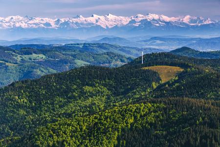 風光明媚な夏の山の緑のある風景の丘とスイス アルプスに対してバック グラウンドでの風車。グリーン エネルギーと持続可能性の概念。