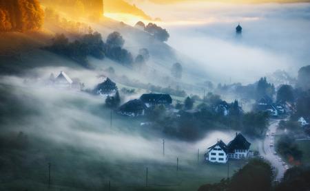 夕暮れの秋の山の風景。歴史的な村黒い森は、霧に覆われています。カラフルな夢のような旅行の背景。 写真素材