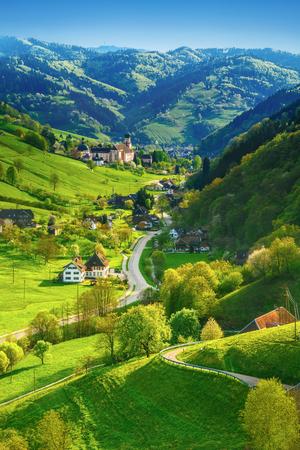 美しい夏の風景: 絵のような田園地帯、古い教会の緑山の谷。ドイツの黒い森。カラフルな夏の背景。