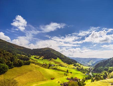 風光明媚な夏の風景: 古い歴史的な村や放牧牛の緑の山の谷。平和的なカラフルなのどかな田園。旅行やバック グラウンドをハイキングします。 写真素材