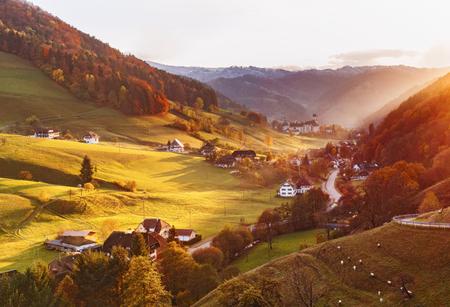夕暮れの秋の美しい山あいの風光明媚なパノラマの景色。山林、民家、古い修道院とカラフルな田舎風景。ドイツの黒い森。