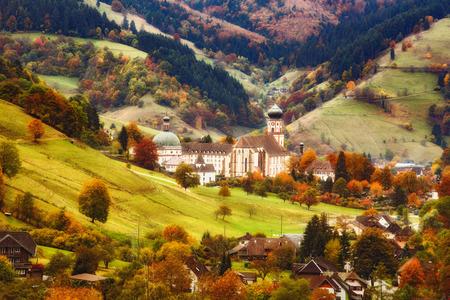秋の美しい山あいの風光明媚なパノラマの景色。山林、民家、古い修道院とカラフルな田舎風景。ドイツの黒い森。旅行やバック グラウンドをハイ
