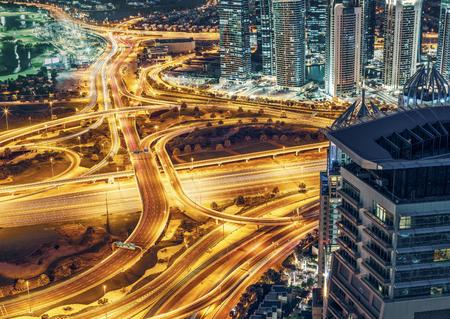 夜市イルミネーションとスクレーパー アラブ首長国連邦、ドバイの大規模な高速道路ジャンクションの空撮。旅行と交通のカラフルな背景。 写真素材