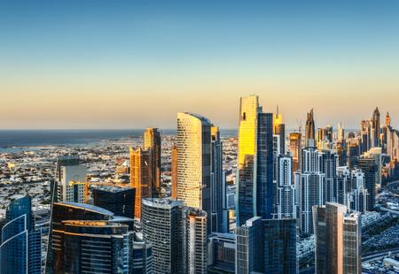 日没で近代的な都市建築。ドバイのビジネス湾タワーの昇格を表示します。