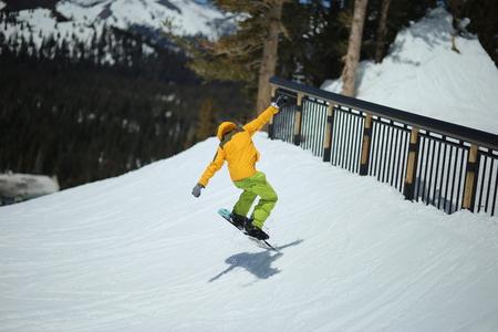 Snowboarder having fun, jump. Male wearing bright yellow winter jacket