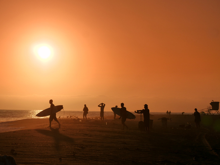 People watching sunset on the beach, surfer walking to the ocean. Photographer shooting sun. Imagens
