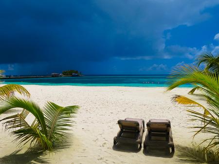 맑음, 열 대 해변 전에 어두운 하늘입니다. 완전한 행복, 기쁨, 평화의 장소. 몰디브에서 하얀 해변에 두 비치의 자입니다. 천국 엽서