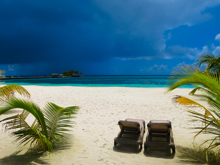Dark sky before thunderstorm, tropical beach. Place of complete bliss, delight, peace. Two beach chair on white beach in Maldives. Heaven postcards