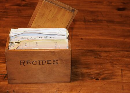 recipe: An old, wooden recipe box stuffed with recipes. Stock Photo