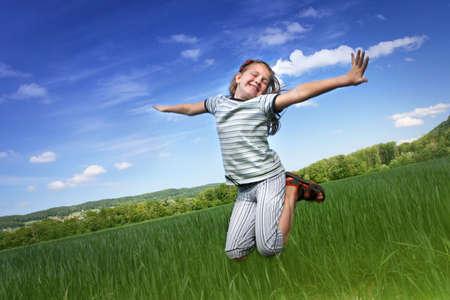 enfant qui court: Bonne fille de sauter dans le domaine Banque d'images