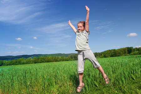 Happy girl jumping in field