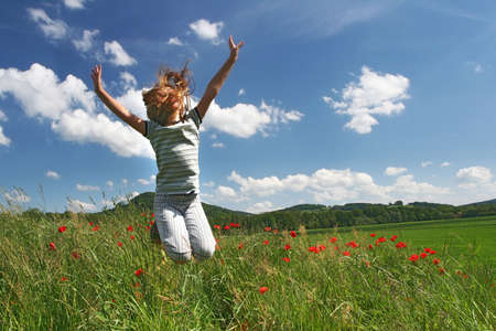 Happy jumping girl on the red poppies field photo