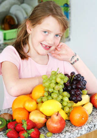 Girl with fruits assortment in the kitchen photo