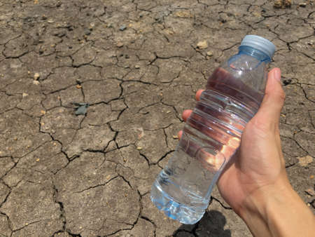 environmental concern: A water bottle on dry and cracked ground