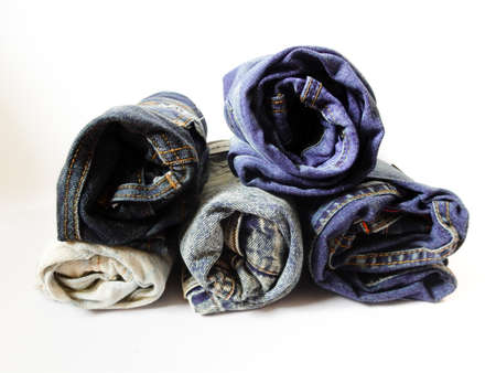 pile of different jeans isolated on white background