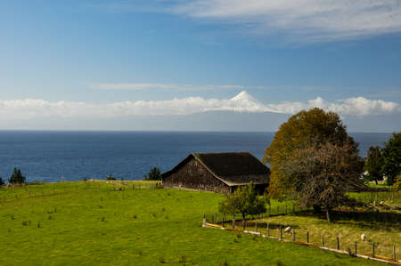 Old Wooden Barn with view over Osorno Volcano, Puerto Varas, Chile.