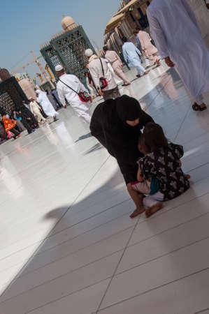 cooperating: Mother grabbing children not cooperating, Saudi Arabia.