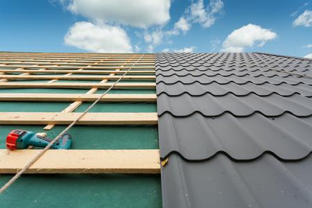 Huis onder construction.Roof met metalen tegel, schroevendraaier en dakbedekking ijzer