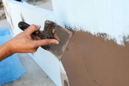 skimming: Man hand with trowel plastering a wall Stock Photo