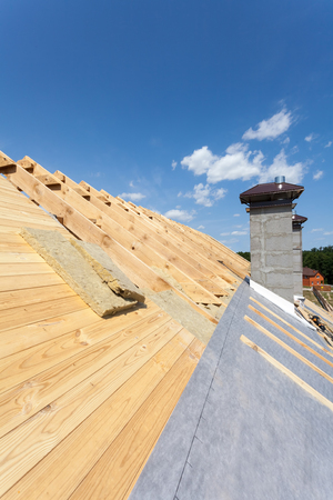 roofing membrane: Roof insulation. New wooden house under construction with chimneys against blue sky