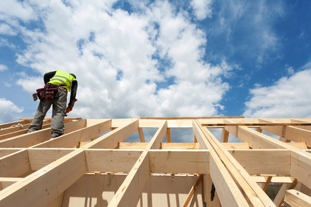 푸른 하늘에 대하여 지붕에서 일하는 건설 승무원