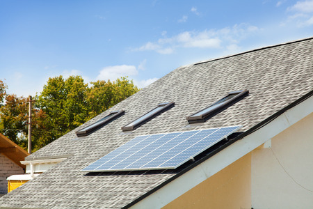 Solar water panel heating on new house roof with skylights against blue sky