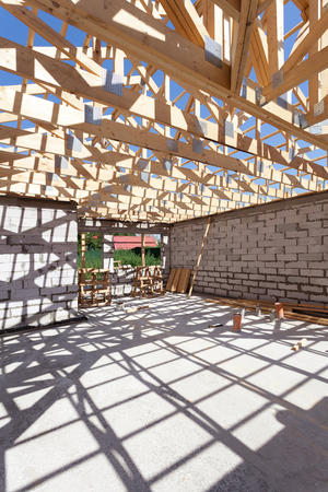 roof framing: New residential wooden construction home framing. Building a roof with wooden balks