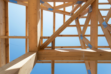 timber frame: New residential wooden construction home framing against a blue sky