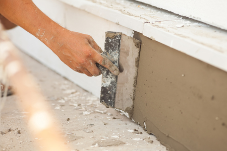 patching: Man hand with trowel plastering a foundation of house