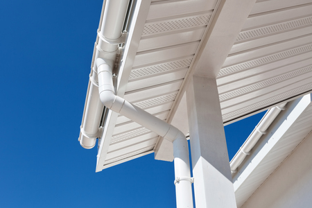 New rain gutter on a home against blue sky Imagens